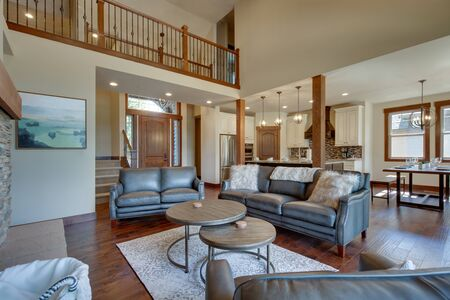 Photo pour An absolute beautiful luxury living room with huge vaulted  ceiling, fire place, harwood floor, amazing furniture, and lots of windows and doors. Solid wood rustic modern dining room table. - image libre de droit