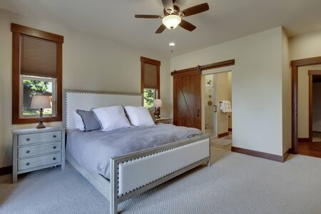 Photo pour Beautiful large luxury new bedroom with great design, beige, grey and white tones, TV bove dresser, rich wooden doors, window blinds and grey carpet. Cozy and practicle. Expensive furniture. Doors open to back yard patio. - image libre de droit