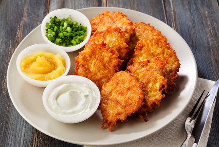 Foto de Potato pancakes, latkes or boxty and sauces from sour cream, yogurt, apple sauce and finely chopped green onion on a wooden table of boards - Imagen libre de derechos