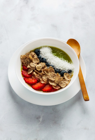 a bowl of smoothies, with cereals for a healthy breakfast and berries, chia seeds and coconut chips freshly sliced fruit, Wheat bran and Cornflake. Served with a wooden spoon on a white marble table