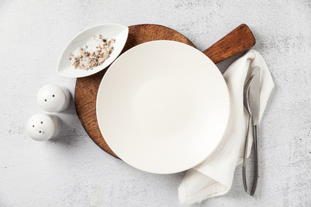Foto de empty plate and cutlery on a wooden cutting board. a fork, a knife and a salt bowl with a pepper shaker. on white stone background, napkin. the table is set for breakfast or lunch - Imagen libre de derechos