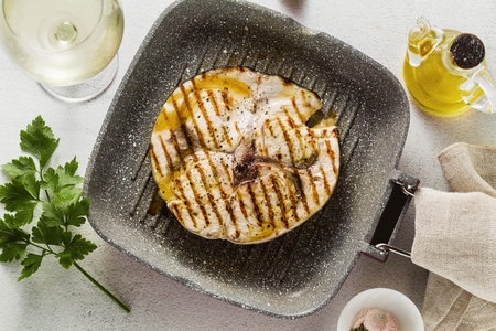 Photo pour swordfish steak fried  on grill pan with olive oil and spices. white wine glass - image libre de droit