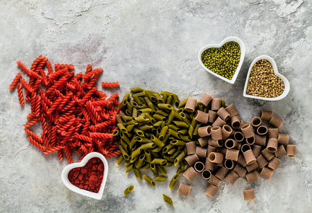 multicolor gluten-free pasta with ingredients in bowls in the form of hearts from which it is made on a stone table