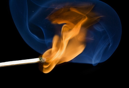 Lighted match and blue smoke on a black background