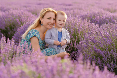 Foto für Happy young mother and her little son posing in purple field of lavender flowers - Lizenzfreies Bild