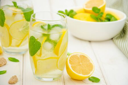 Photo pour Homemade lemonade with lemon slices, mint and brown sugar in a glass with ice on a white wooden background. Horizontal orientation. - image libre de droit