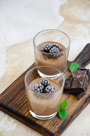 Photo pour Italian dessert - chocolate panna cotta, mousse, cream or pudding with blackberry in a glass on a board on a light concrete background. Vertical orientation. Copy space. - image libre de droit