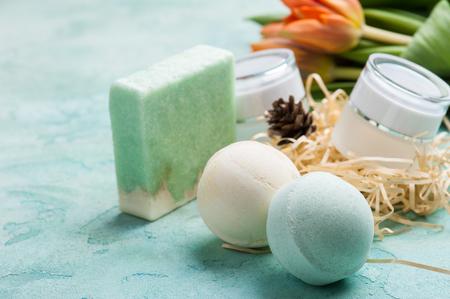 Photo pour Green bath bomb and soap with SPA products on blue concrete background. Bathroom composition - image libre de droit