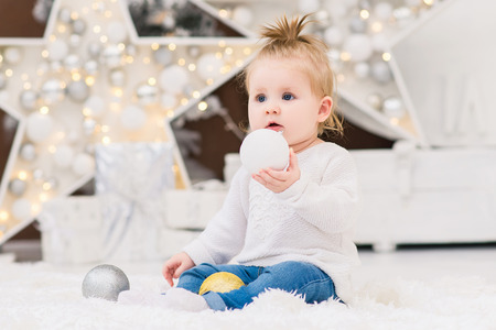 Foto de Little cute baby girl sits in a white sweater on a background of Christmas trees, lights, garlands, Christmas balls and gift boxes. New Year and Christmas holidays. - Imagen libre de derechos