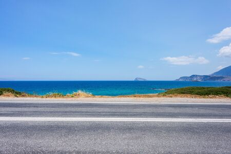 Foto per ?ar travel concept on Crete island, Greece. landscape of blue sea, sky, mountains, against the background of the road - Immagine Royalty Free