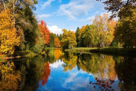 Foto de Autumn foliage in Pavlovsky park, Pavlovsk, Saint Petersburg, Russia. Autumn park with pond. Sky is reflected in water. - Imagen libre de derechos