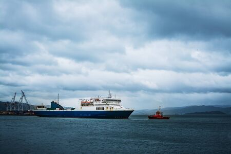 Photo pour Bright red tugboat pulling a large interislander ferry out from Wellington Port on a stormy winter day - image libre de droit