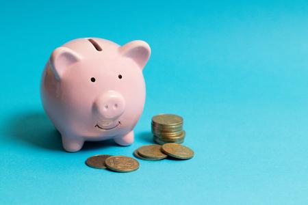 Photo pour Piggy bank with gold coins on blue background. Commercial concept. - image libre de droit