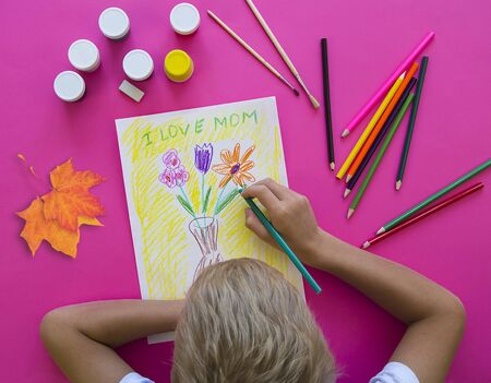 Photo pour A child draws flowers as a gift to his mother to give on mother's Day.Happy family concept. Mother's day.Flat position, top view-image - image libre de droit