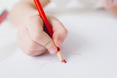 Photo pour Child is holding a red pencil with a broken rod. Selective focus. - image libre de droit