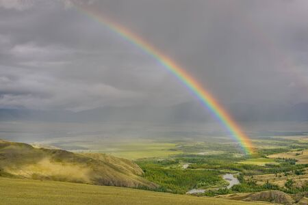 Amazing bright colorful rainbow over the mountains, a valley with a winding river and forest against a stormy sky with clouds and rain. Altai, Russia.