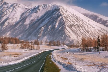 Photo pour Picturesque winter landscape with the asphalt road in the mountains covered with snow and trees on the side of the road on the background of the blue sky and clouds - image libre de droit