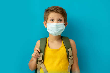 Foto de Schoolboy in a medical mask with a backpack. Back to school. Copy space. Blu background - Imagen libre de derechos
