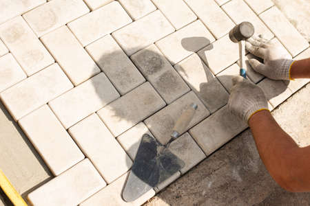 Photo for The master lays paving stones in layers. Garden brick pathway paving by professional paver worker. Laying gray concrete paving slabs in house courtyard on sand foundation base. - Royalty Free Image