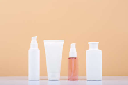 Photo pour Skin care products in a row on white table against beige background. Beauty and cosmetic concept - image libre de droit