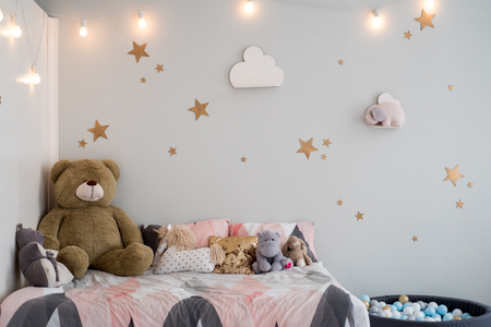 Photo pour Teddy bear between paper bags and wooden chairs in child's room - image libre de droit