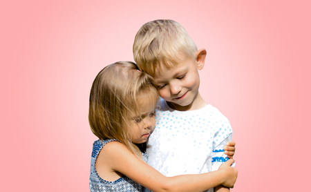 Photo pour Two cute funny kids standing together and hugging. Innocent children's love. Isolated pink background. - image libre de droit