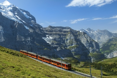 red train on the background of snowy peaks in the Swiss Alps