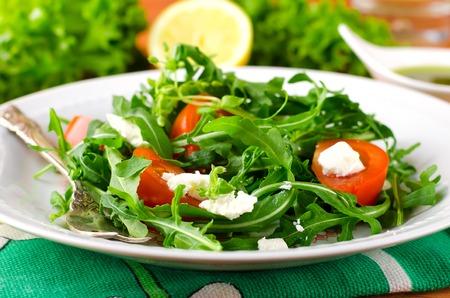 Foto de Green salad with arugula, tomato and feta cheese. Italian cuisine - Imagen libre de derechos