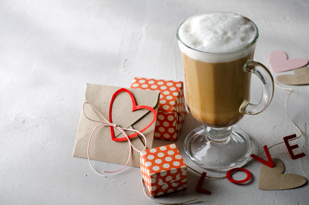 Coffee Latte with gift boxes, envelope and paper hearts. Pink, red, white colors on bright background. Love, Valentines day concept. Copy space