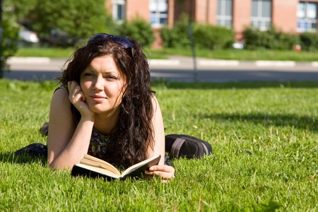 High school student, lying in grass on school campus reading a book. Student studying on the grass. Beautiful young woman reading book at park