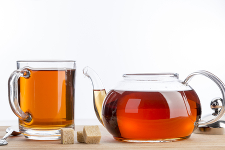 Photo for Transparent teapot and cup of black tea - Royalty Free Image
