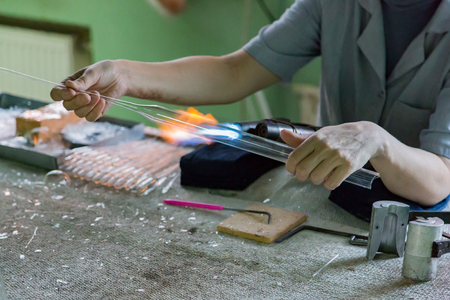 Glassblower woman works with a gas burner and a fragile glass billet