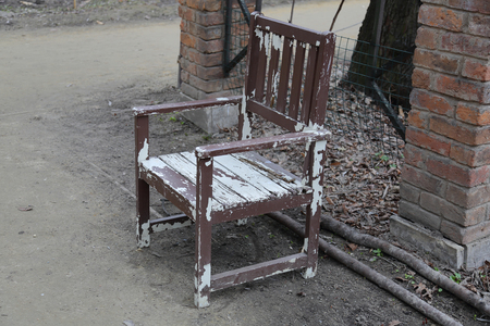 Old dirty wooden chair doused with white paint