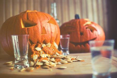 Pumpkin puking with pumpkin seeds on wood table, vodka, vintage effect