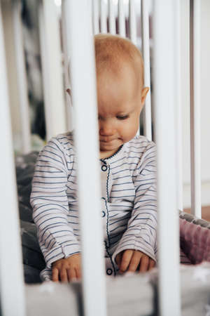 Photo pour baby girl with blue eyes and blond standing in her bed, sad and crying - image libre de droit
