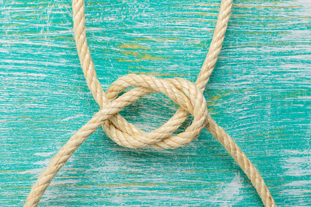 Ship rope knot on turquoise wooden background. Top view.