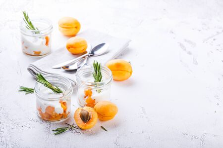Photo pour Natural yogurt with pieces of apricots, Walnut and rosemary in mini glass jars on light background. - image libre de droit