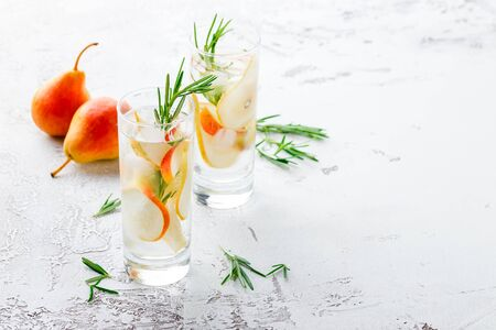 Summer drinks, rosemary pear cocktails with ice in glasses. Refreshing summer homemade Alcoholic or non-alcoholic cocktailsor Detox infused flavored water. Space for text.