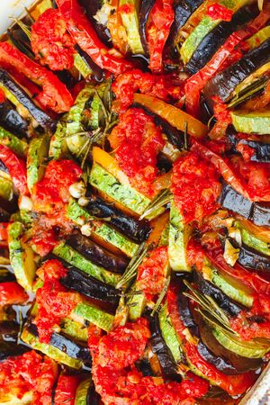 Photo pour Vegetarian ratatouille from eggplants, zucchini, tomatoes and bell pepper sauce and tomato with herbs in ceramic form before baking. Top view. Close up. - image libre de droit