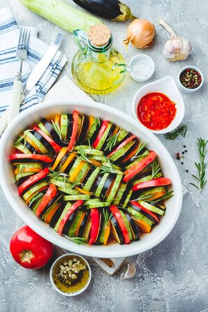 Photo pour Vegetarian uncooked ratatouille from eggplants, zucchini, tomatoes and bell pepper sauce and tomato with herbs in ceramic form before baking. Top view. Rustic style. - image libre de droit