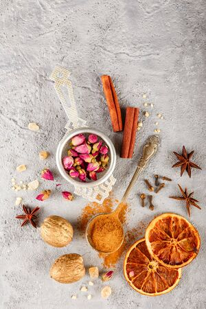 Photo pour Different kinds of spices - cinnamon, anise stars, cloves, walnuts, dried orange slices, caramelized brown sugar and dried rose buds on a gray concrete background. Top view with copy space - image libre de droit