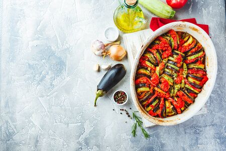 Foto de Vegetarian ratatouille from eggplants, zucchini, tomatoes and bell pepper sauce and tomato with herbs in ceramic form before baking. Top view. Rustic style. - Imagen libre de derechos