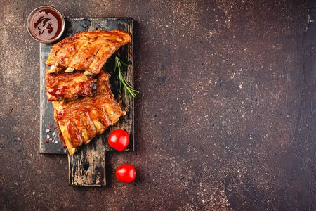 Photo pour Grilled pork ribs on a wooden cutting board on a brown background. Top view. Space for text. - image libre de droit