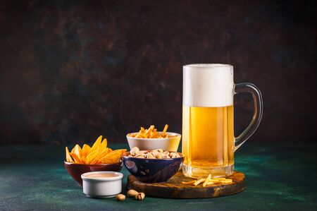 Foto de Glass mug with beer with foam and water drops and snacks on a dark green background - Imagen libre de derechos