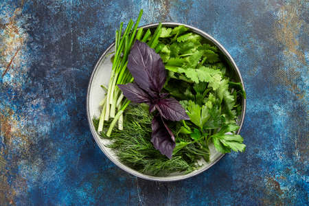 Foto für Plate with parsley, dill, cilantro, green onions, red basil on blue background, top view - Lizenzfreies Bild
