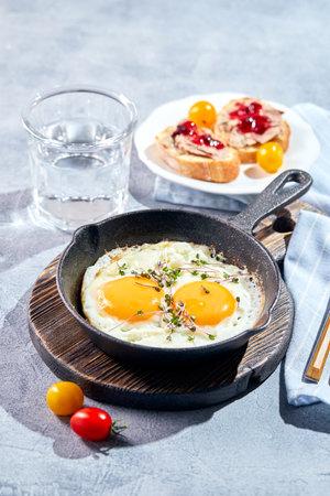 Photo pour Fried eggs in cast-iron skillets. Sunny morning breakfast concept - image libre de droit