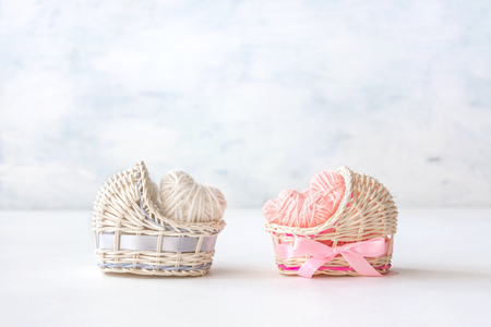 Photo pour Baby shower ideas for a girl and boy party. Pink and blue decorative straw cradles with thread hearts and text BOY or GIRL. - image libre de droit