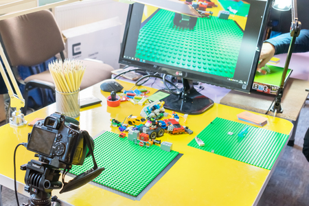 KROPIVNITSKIY, UKRAINE – 12 MAY, 2018: Stop motion animation process with Lego details and toy cars. Computer monitor, stop motion elements to create animations using a DSLR camera on table