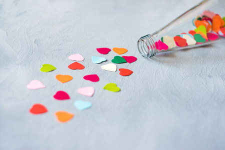 Foto de Valentines day creativity, DIY craft gift, card ideas. Many multicolored paper hearts are poured from glass transparent bottle on grey cement background. Minimal, Love, romance, handmade concept - Imagen libre de derechos