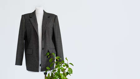 Photo for Sustainable fashion, organic clothes, eco clothing, ecology, sustainability, responsible fashion, 100 cotton. Formal Bio fabric suit with green plants on light background. - Royalty Free Image